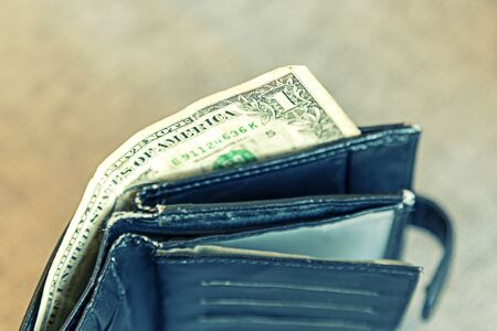 Empty male wallet with one dollar bill. financial wellness. copy space.