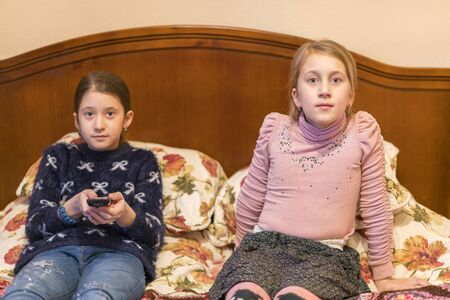 Two girls in bed are watching TV. Cute little girls sitting on a bed together watching television. The concept of children's dependence on television.