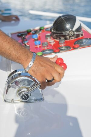 Captain at the helm yacht. Mens hand drives a yacht. concept of sea recreation and tourism. vertical photo.