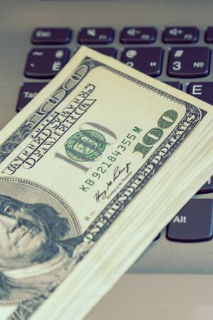 A pack of hundred dollar bills on the keyboard. Online business - notebook keyboard and US dollars. Freelancer concept. Vertical photo