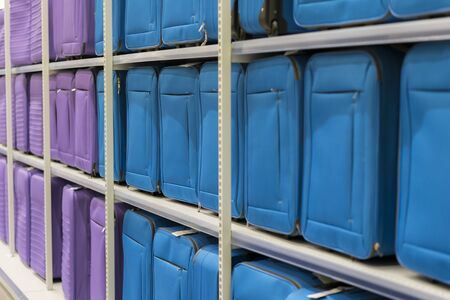 Blue and purple suitcases on a shelf in a store. Travel concept.