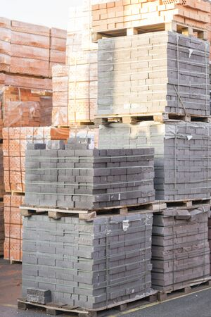 Several pallets with concrete brick stacked on top of each other in depot. Industrial production of bricks. vertical photo. Stock fotó