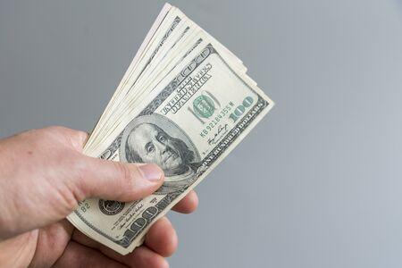 hand holding money us dollar on grey background. Image of hand holding 100 Dollar bills. money in hand.