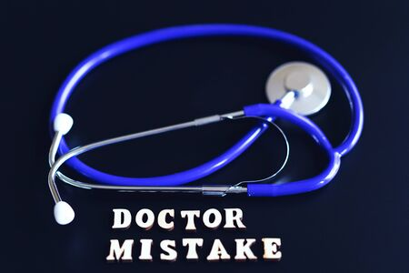 doctoral mistake concept. The inscription mistake and a stethoscope on a black background. toned.