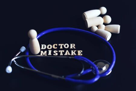doctoral mistake concept. The inscription mistake and a stethoscope on a black background. Doctoral Mortality. toned.