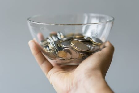 coins in a piggy bank vase. saving money in jar with American dollors , cash. Concept of accumulating money on a gray background.