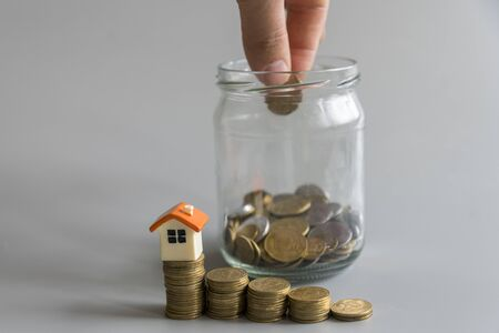 Real estate investment. Saving to buy a house that hand putting money coins ,saving money or money growth concept.