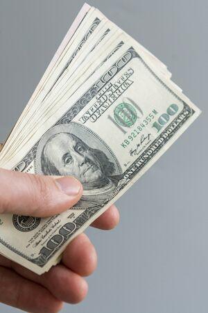 hand holding money us dollar on grey background. Image of hand holding 100 Dollar bills. money in hand. vertical photo. Stock fotó