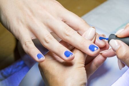 The concept of hand care. Closeup manicurist applies nail gel polish on middle finger. Beautician gently manicured service. Nail polish being applied to hand, polish is a blue color.