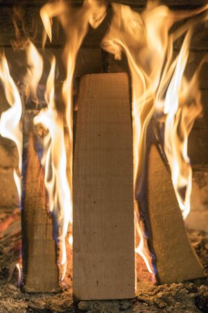 A fire burns in a fireplace, Fire to keep warm. Close up shot of burning firewood in the fireplace. vertical photo.
