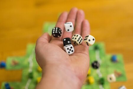 Hand throws the dice on the background of colorful blurred fantasy Board games, gaming moments in dynamics. selected focus.