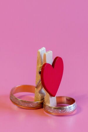 Wedding rings with a heart on a pink background. Love and marriage concept. Close up and top view of golden wedding rings and heart, isolated, copy space. vertical photo.