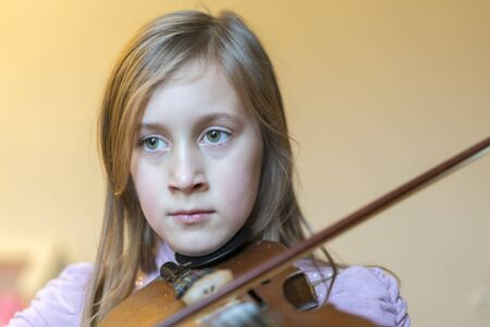 little girl playing the violin at home. Child or little girl playing violin indoors at home. copy space