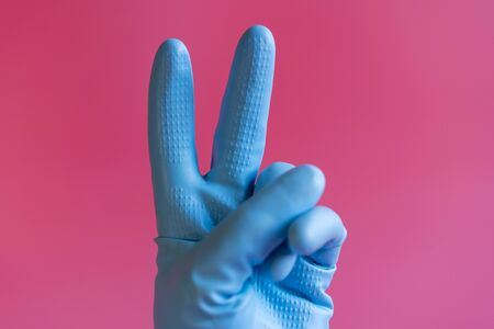 Hand with cleaning glove making peace. Hand in a rubber glove on a pink background.