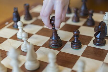 Businessman hand holding chess pieces on board with white background, challenges planning business strategy to success. playing wooden chess pieces.