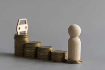 Saving money for car or trade car for cash, finance concept. Human figure, a stack of coins and a car model On a gray background.