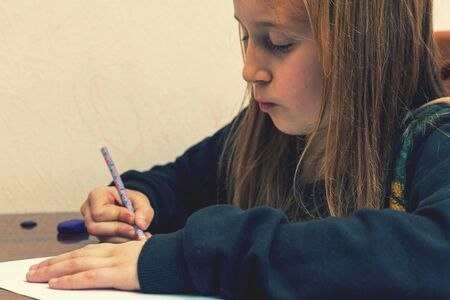 Schoolgirl draws at a desk. Little girl student studying sitting at her desk. School, education, knowledge and children. toned Banque d'images - 141862419