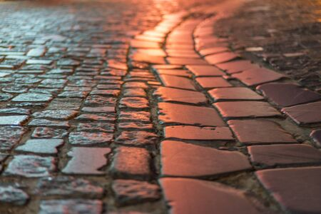 Paving stone vintage road cover. Evening road in a historical place. texture paving stones night road.