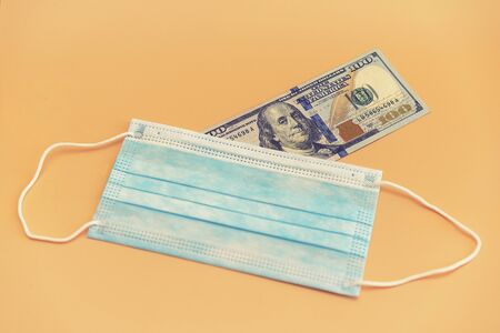 Medical mask and one hundred dollars on an orange background. Medical face masks and money. Surgical face mask. COVID-19 has caused a shortage of face masks.