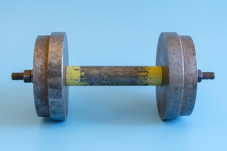 Iron dumbbell on a blue background. Sport and healthy lifestyle concept.