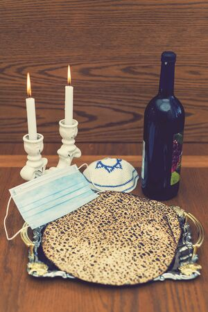 Jewish holiday Passover banner design with wine, matzo and. Kipa and protective medical mask. Protective medical mask. Concept Passover during quarantine. vertical photo.