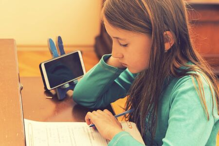 Home schooling. schoolgirl studying homework math during her online lesson at home, social distance during quarantine, self-isolation, online education concept, home schooler