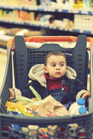 Beautiful baby in shopping cart - trolley. toned