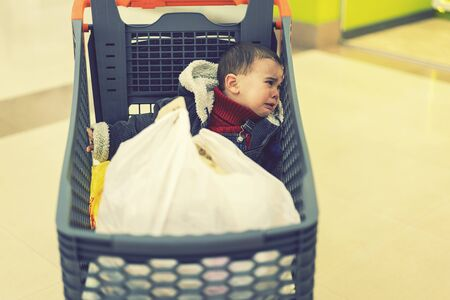 baby boy crying in a supermarket in a cart. The Forgotten Child. toned