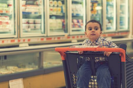 Baby boy rides in a trolley through a shopping center. toned