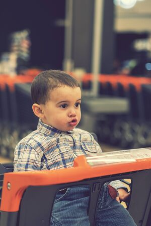 Toddler in the cart in the supermarket. toned. vertical photo. toned