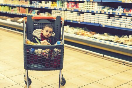 Beautiful baby in shopping cart - trolley. A trolley with products in which the child sits. Full cart with food in the supermarket. In the cart sits a baby. toned Stock fotó