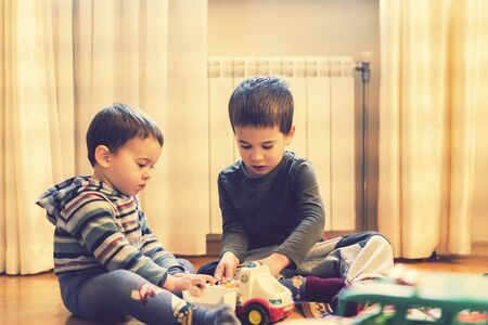 Two little brothers play in the playing room with an ambulance. toned