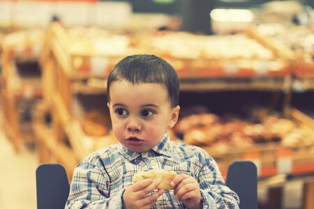 Cute boy eating a bun or pita bread in a supermarket in the cart. Hungry child in the store. toned Stock fotó