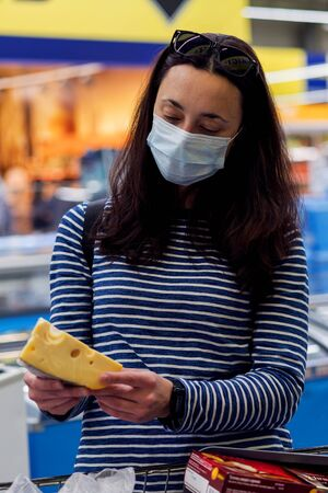 woman in protective medical mask in a supermarket chooses cheese. pandemic and covid-19 concept. Hand of the buyer with a piece of cheese in the store. vertical photo 免版税图像