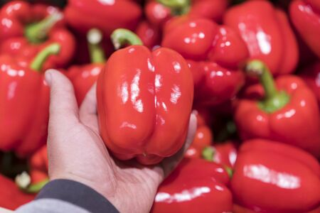 A man chooses red bell peppers in a grocery store, at the market. Hand take the pepper from a vegetable basket. Mans hand is holding Red Bell pepper from supermarket shelf. close-up