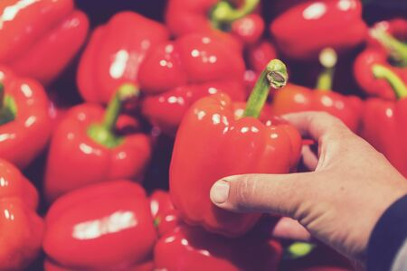 A man chooses red bell peppers in a grocery store, at the market. Hand take the pepper from a vegetable basket. Mans hand is holding Red Bell pepper from supermarket shelf. close-up. toned Stock fotó