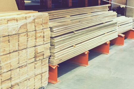 Many wooden planks in hardware store. Stacks of wooden planks at building materials store. Boards in a hardware store. Repair and construction concept. toned.