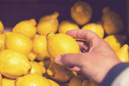 man choosing fresh lemons in supermarket. Man's hand takes a fresh lemon from the food shelf. Organic products. Vegetables and fruits. Healthy food. Shopping in the supermarket. toned. 免版税图像