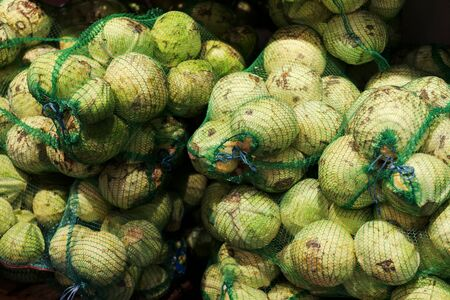 old white cabbage in bags. cabbage in bags at the market. The vendors use the bamboo strips to make a loop for carrying. forks of cabbage in nets harvesting for the winter, farming. toned. 免版税图像