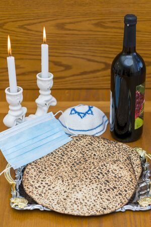 Corona Passover. Dust mask, bottle of wine and matzah - a traditional Jewish food for Passover. Small Passover Seder in the Corona Virus era. Due to Covid-19 quarantine. 免版税图像