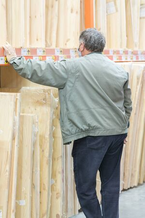 man in a protective medical mask in a hardware store chooses boards. man is protected from the coronovirus. vertical photo.