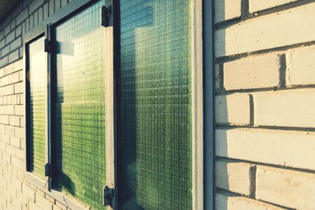 Green window with bars in a white brick building. toned.