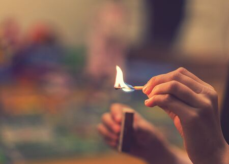 The child lighting the matches. The fire in the hands of a child. Dangerous situation at home. A small child plays with matches, a fire, a fire flares up, danger, child and matches, toned.