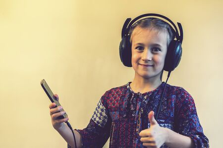 Little Girl Headphones Using Phone. thumbs up. toned
