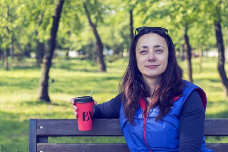 Beautiful Caucasian woman with long brown hair sitting in the park drinking a cup of tea or coffee and smiling. Middle-aged athletic woman with long hair drinks coffee in a park. toned