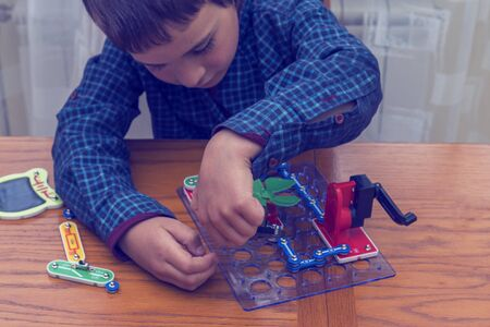 The boy playing an electric constructor. The child is played by intellectual toys. A boy in a blue shirt masters electronics. The concept of early development of children. toned.