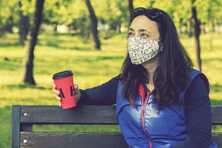 Woman relaxing in a spring park in a protective surgical face mask sitting on a bench in the sunshine during the coronavirus drinking coffee. toned.