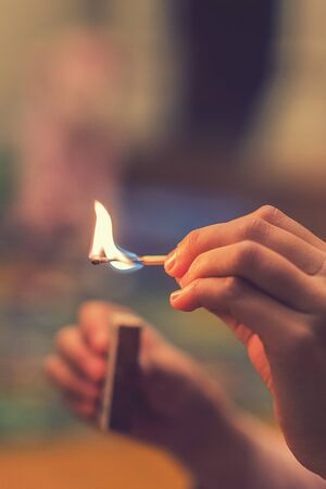 The child lighting the matches. The fire in the hands of a child. vertical photo. toned.