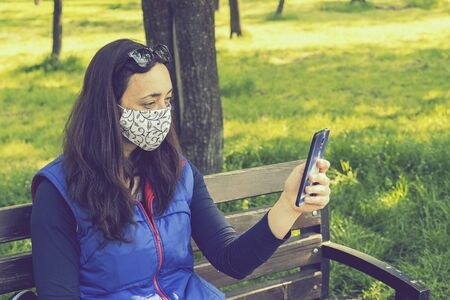 The woman sitting on the bench in the park and wearing a protective mask and using smartphone . Coronavirus concept.