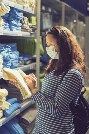 Woman in medical mask choosing goods in a store. Concept of shopping during quarantine at covid-19 pandemic. shopping at the time of the coronavirus. Beautiful young women in a flu mask.